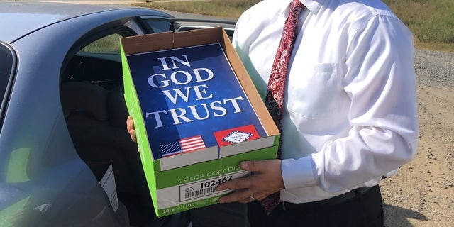 """Arkansas Rep. Jim Dotson shows off new """"In God We Trust"""" posters that will be hung in schools."""