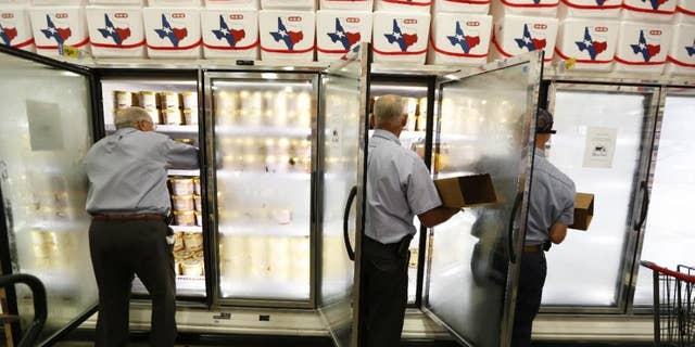 Blue Bell personnel Freddie Hugo, from left, Rickey Seilheimer, and Charlie Franke stock freezers with Blue Bell products early Monday, Aug. 31, 2015, in Brenham, Texas. Blue Bell Creameries resumed selling its products at select locations Monday, four months after the Texas-based retailer halted sales due to listeria contamination. Blue Bell ice cream is now available at stores in the Houston and Austin areas, including in the company's hometown of Brenham, plus parts of Alabama. (Steve Gonzales/Houston Chronicle via AP)
