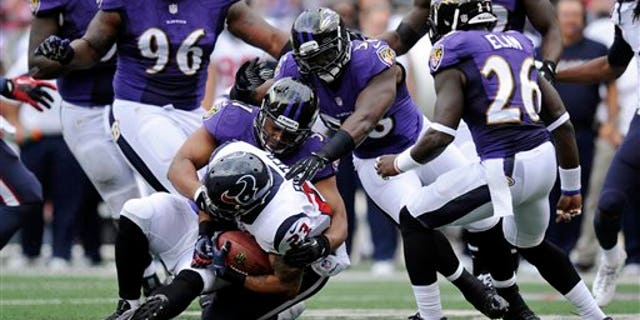 Houston Texans running back Arian Foster, bottom, is tackled by a pack of Baltimore Ravens defenders in the first half of an NFL football game Sunday, Sept. 22, 2013, in Baltimore. (AP Photo/Nick Wass)