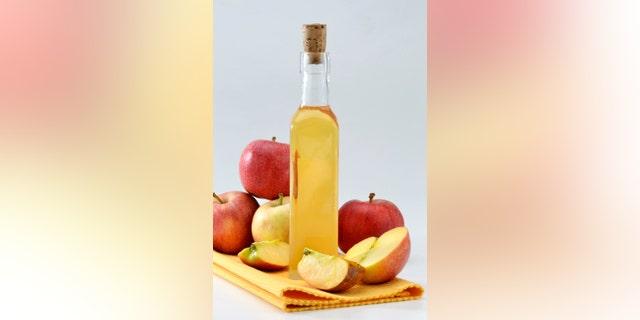 Cider vinegar bottle and red apples.
