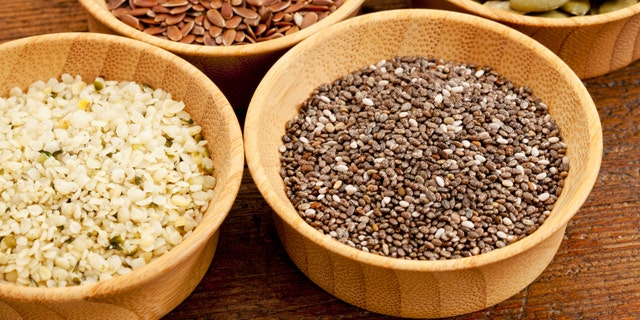 chia, hemp, flax and pumpkin - healthy seeds in small wooden bowls