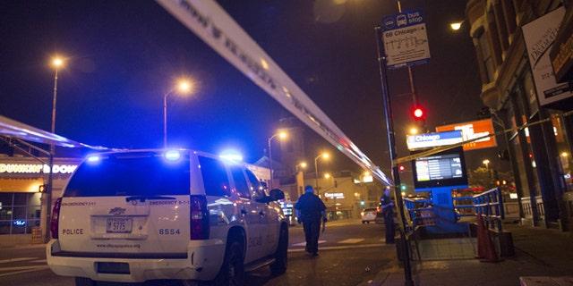 Chicago police officers investigate the crime scene of a gunshot victim.