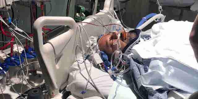 Rickey Fievez, paralyzed from the neck down, remains hospitalized after being shot by a carjacking suspect who was ultimately killed.
