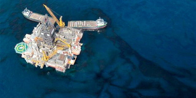 Oil floats around a rig at the site of the Deepwater Horizon oil spill in the Gulf of Mexico May 31. (AP Photo)