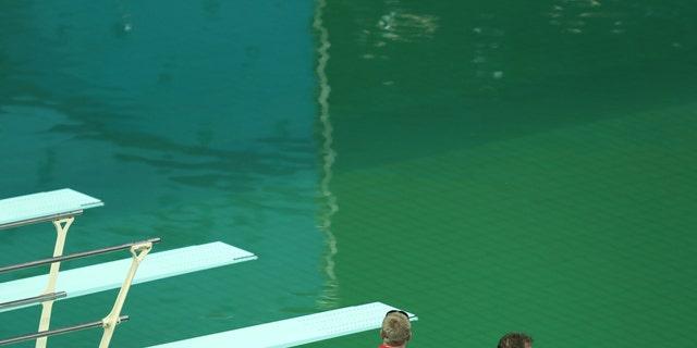 Maria Lenk Aquatics Centre - Rio de Janeiro, Brazil - 09/08/2016. Officials look at the Olympic diving pool (REUTERS/Antonio Bronic)