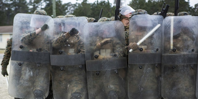 U.S. Marines with Battalion Landing Team, 1st Battalion, 6th Marine Regiment, 22nd Marine Expeditionary Unit (MEU), hold riot shields to prevent injury during a simulated riot at Camp Lejeune, N.C., Jan. 22, 2016. The Marines participated in the course to ensure mission readiness and to improve their ability to maintain control during a riot. (Credit: U.S. Marine Corps)