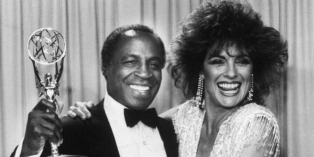 Robert Guillaume accepts his Emmy award for his role on 'Benson' alongside Linda Grey in 1985.