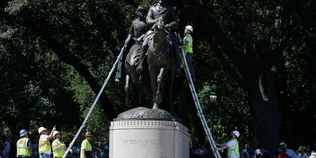 Workers inspect a statue of Robert E. Lee in a public park in Dallas, Sept. 6, 2017.