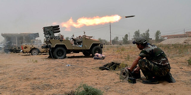 Iraqi forces fire rockets during battle against Islamic State.