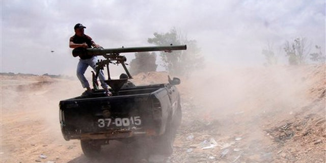 Libyan rebel fires a rocket toward pro-Muammar Qaddafi forces on the front line of Dafniya in Misrata, Libya, June 21.
