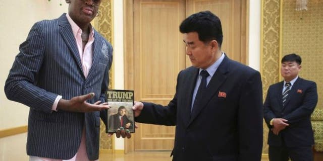 """Dennis Rodman presents a book titled """"Trump: The Art of the Deal"""" to North Korea's Sports Minister Kim Il Guk in June 2017."""