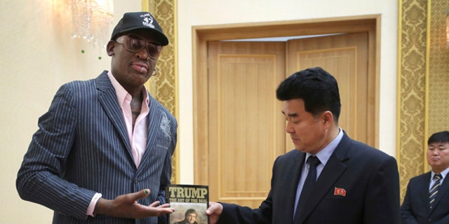 """Dennis Rodman presents a book titled """"Trump The Art of the Deal"""" to North Korea's Sports Minister Kim Il Guk in Pyongyang."""