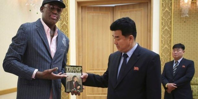 "Dennis Rodman presents Donald Trump's ""Art of the Deal"" to North Korean Sports Minister Kim Il Guk in June 2017."