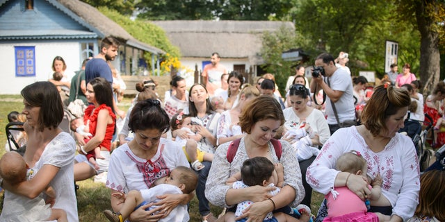 Women breastfeed their babies at an event promoting the freedom of mothers to breastfeed in public, during World Breastfeeding Week at the Village Museum in Bucharest, Romania, Saturday, Aug. 6, 2016. (AP Photo/Andreea Alexandru)
