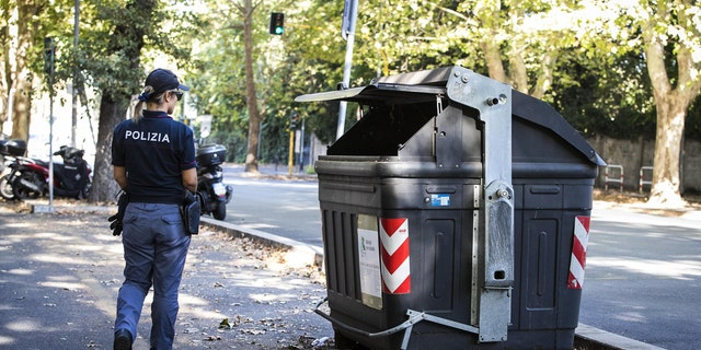 An Italian police officer walks past the site where a trash bin was removed after two amputated legs were found.