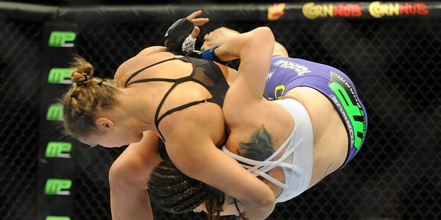 Jul 5, 2014; Las Vegas, NV, USA; Ronda Rousey (red gloves) takes down Alexis Davis (blue gloves) during the first round of a bantamweight fight at Mandalay Bay Events Center. Mandatory Credit: Stephen R. Sylvanie-USA TODAY Sports - RTR3XAV1