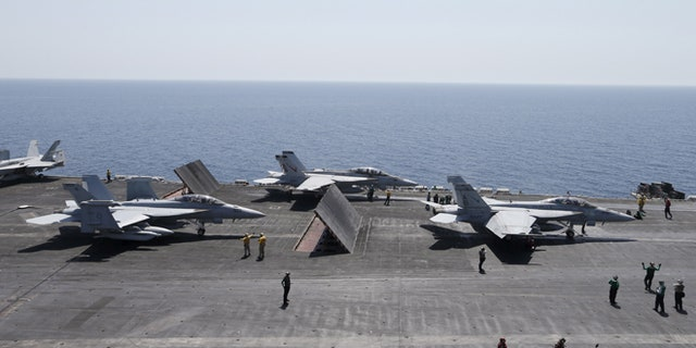 June 18, 2015: F/A-18E/F Super Hornets of Strike Fighter Attack Squadron 211 (VFA-211) are lined up for take off on the flight deck of the USS Theodore Roosevelt (CVN-71) aircraft carrier in the Gulf.