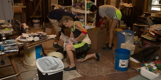 Rosalea Nall and volunteers work to clean up and rebuild her devastated home.
