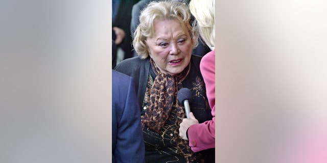 """FILE- In this April 1, 2002, file photo, actress and comedian Rose Marie talks to the press as she arrives for a ceremony honoring comedian Milton Berle at Hillside Memorial Park and Mortuary in Los Angeles. Family spokesman Harlan Boll said Marie, the wisecracking Sally Rogers of """"The Dick Van Dyke Show,"""" died Thursday, Dec. 28, 2017. She was 94. (AP Photo/Nick Ut, File)"""