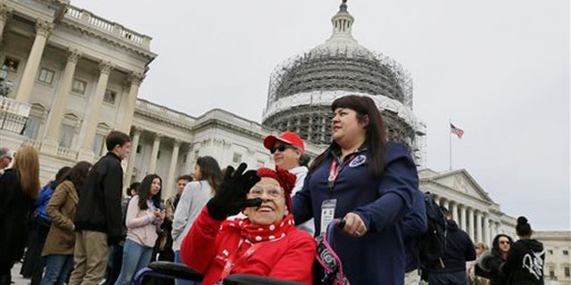 """Former Rosie, Cookie Garza, 96, pushed by her granddaughter Stephanie Hagaman, waves on the Capitol grounds, Tuesday, March 22, 2016 in Washington. Seven decades after their """"we can do it"""" attitude proved invaluable to the Allied victory in World War II, about 30 """"Rosie the Riveters"""" were honored Tuesday with a visit to Washington.   (AP Photo/Carlos Osorio)"""