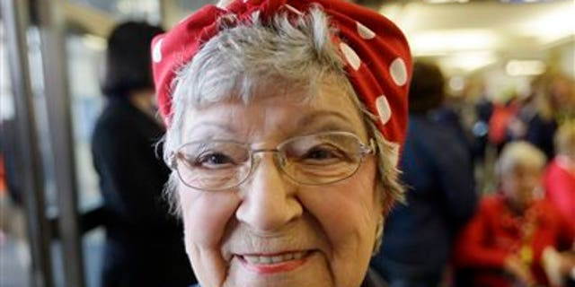 """Former Rosie, T. Ogden of Aurora, Ill. shows a photo of herself after greeting fellow Rosies from Michigan on their arrival at the Ronald Reagan Washington National Airport, Tuesday, March 22, 2016 in Washington. Seven decades after their """"we can do it"""" attitude proved invaluable to the Allied victory in World War II, some """"Rosie the Riveters"""" are being honored with a flight to Washington, D.C. The women will check out the National World War II Memorial and Arlington National Cemetery, and have lunch with members of Congress. (AP Photo/Carlos Osorio)"""