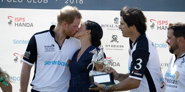 While Prince Harry was being presented his polo-winning trophy, he appeared to be a bit distracted by his wife.