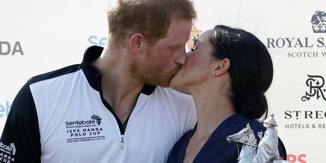 Meghan, Duchess of Sussex and Britain's Prince Harry kiss during the presentation ceremony for the Sentebale ISPS Handa Polo Cup at the Royal County of Berkshire Polo Club in Windsor, England, July 26, 2018.