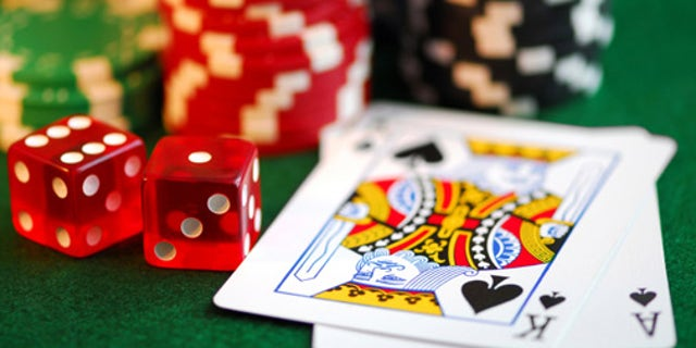 Stacks of gambling chips, playing cards and dice on green background