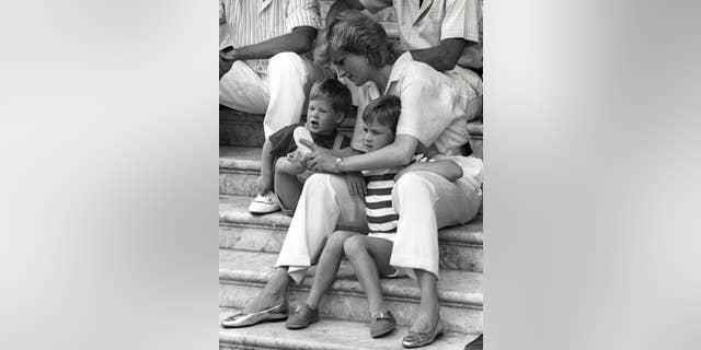 Princess Diana puts on shoes for little Prince Harry as her other son Prince William squints from the bright sun during their vacation with the Spanish royal family at Marivent Palace in Palma De Mallorca.