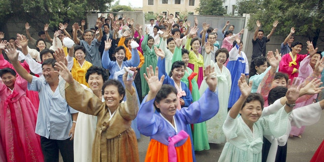 North Koreans wave to South Koreans after they read joint mass with