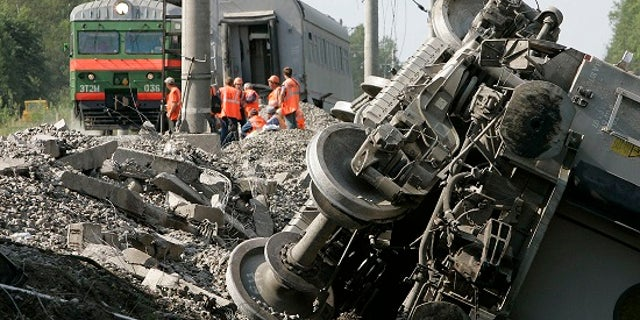 Rescuers work at the site of a train that derailed northwest of Moscow after a bomb exploded.