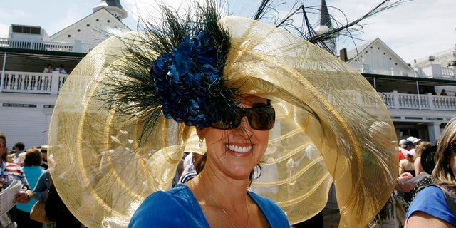Race fan Julie Casteel displays her hat before the 134th running of the Kentucky Derby horse race.