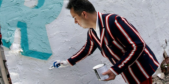 """Artist Stephen Powers touches up a mural which is part of the """"Love Letters """" 50 mural project in Philadelphia, Pennsylvania, July 8, 2009. On the side of a West Philadelphia barber shop, a painted jumble of multicolored letters and a few words mark the start of a massive mural project to celebrate community in one of the city's poorest neighborhoods.  REUTERS/Tim Shaffer (UNITED STATES SOCIETY ENTERTAINMENT) - RTR25I0S"""