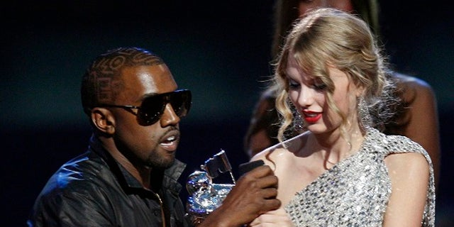 Kanye West takes the microphone from best female video winner Taylor Swift as he praises the video entry from Beyonce at the 2009 MTV Video Music Awards in New York, September 13, 2009.     REUTERS/Gary Hershorn (UNITED STATES ENTERTAINMENT IMAGES OF THE DAY) - RTR27T9C
