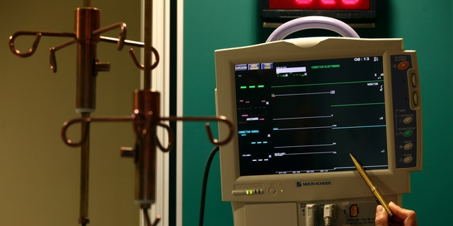 File photo: A nurse points to an Electrocardiograph (EKG) machine with a copper pen next to a copper IV drip stand at the Copper Hospital in Calama city, north of Santiago March 31, 2011.  (REUTERS/Ivan Alvarado)