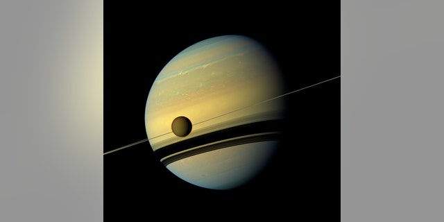 Titan, Saturn's largest moon appears before the planet as it undergoes seasonal changes in this natural color view from NASA's Cassini spacecraft in this handout released by NASA August 29, 2012.