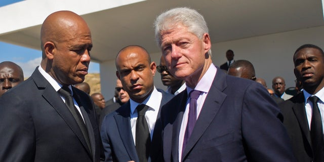 Former President Bill Clinton, right, is seen in this 2013 file photo with Haiti's former President Michel Martelly at a memorial service remembering the lives lost in the January 2010 earthquake.