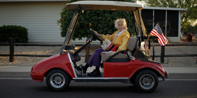 A woman rides in a golf cart with her dog in Sun City, Arizona in 2013.
