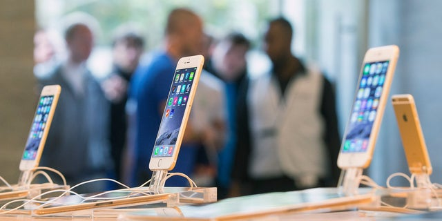 Customers stand in line at the Apple store in Berlin, as they wait to buy the newly released iPhone 6 September 19, 2014.