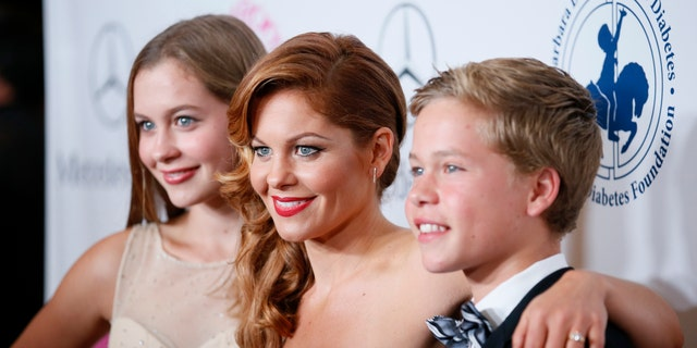 Actress Candace Cameron Bure poses with her daughter and son at The Mercedes-Benz Carousel of Hope Ball to benefit the Barbara Davis Center for Diabetes in Beverly Hills, California October 11, 2014.   REUTERS/Danny Moloshok   (UNITED STATES - Tags: ENTERTAINMENT) - RTR49TPI