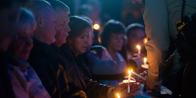 Carl and Marsha Mueller hold candles during a memorial honoring Kayla in February 2015. (REUTERS)