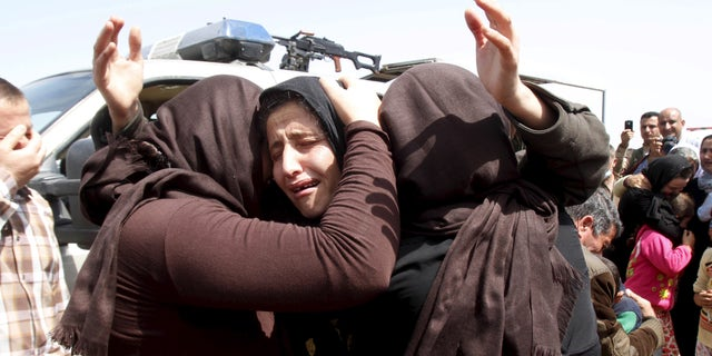 April 8, 2015: Members of the minority Yazidi sect who were newly released from ISIS captivity hug each other on the outskirts of Kirkuk.
