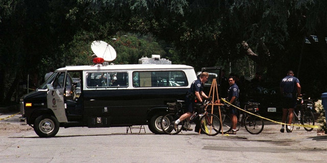 A Los Angeles Police Department van sits in the street near the driveway to the home of actor Phil Hartman May 28, 1998 in Encino, California.
