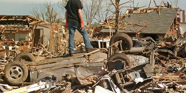 A man stands atop a smashed car in a tornado-ravaged neighborhood south of Oklahoma City. The F5 tornado killed some 44 people in May 1999.