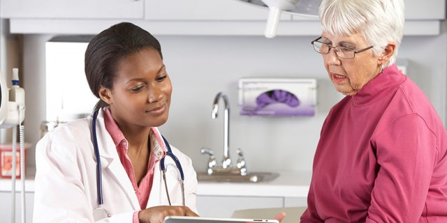 Doctor Discussing Records With Senior Female Patient