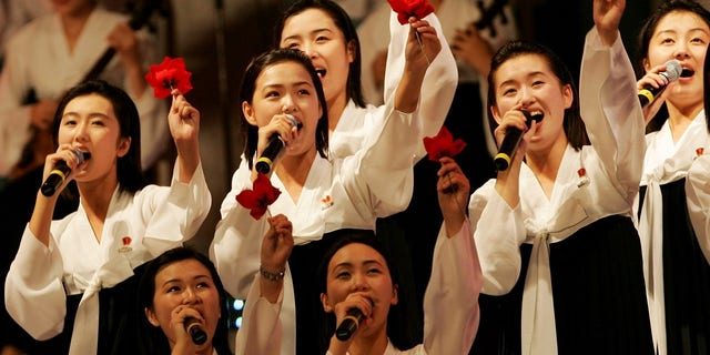 Members of the North Korean cheering squad in traditional costume sing during a cultural performance in Incheon. (Reuters)