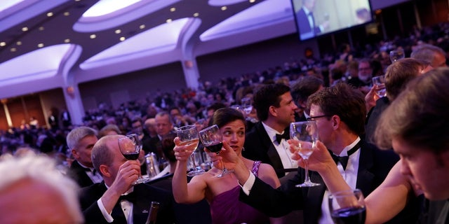 Attendees at the White House Correspondents' Association dinner in Washington raising their glasses.