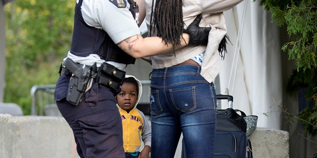 Evanston, whose family stated they are from Haiti, watches as a Royal Canadian Mounted Police officer pats down his mother.