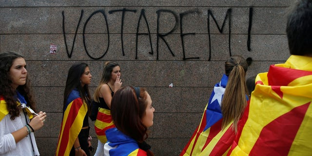 """Students wear Esteladas (Catalan separatist flag) during a demonstration in favor of the banned October 1 independence referendum in Barcelona, Spain. The graffiti on the wall reads, """"We will vote!"""""""
