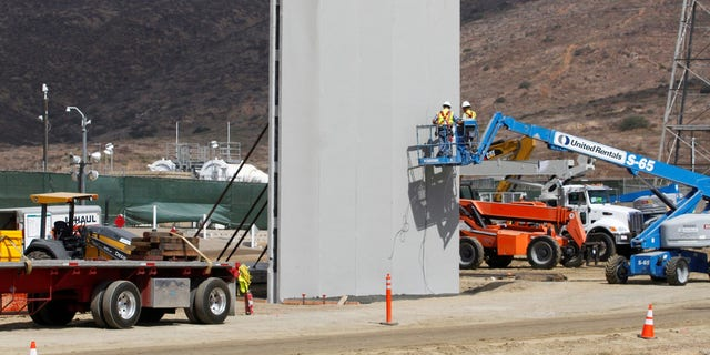 People work in San Diego at the construction site of prototypes for President Trump's border wall with Mexico, in this picture taken from the Mexican side of the border in Tijuana.